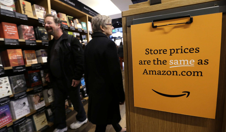 Customers shop at the opening day for Amazon Books, the first brick-and-mortar retail store for online retail giant Amazon, Tuesday, Nov. 3, 2015, in Seattle. The company says the Seattle store, coming two decades after it began selling books over the Internet, will be a physical extension of its website, combining the benefits of online and traditional book shopping. Prices at the store will be the same as books sold online. (AP Photo/Elaine Thompson)